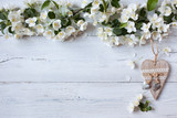 White wooden background with white flowering spring branches and heart