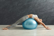 Fitness woman training with fitness ball indoors