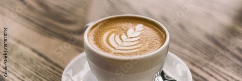 Coffee cup with latte art on cafe wood table banner panorama background.