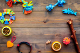 Pet accessories. Toys near bowls with animal feed, collar on dark wooden background top view copy space - 194925306