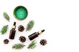 Pine spa cosmetics, products for skin care. Fir essential oil and green aromatic spa salt near branches and cones on white background top view copy space - 194926165
