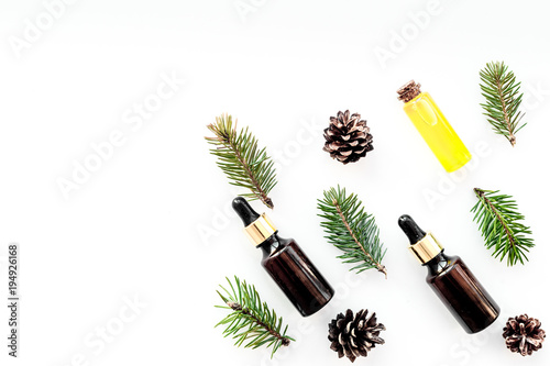 Pine essential oil in bottles on white background top view copy space. Pattern with pine branch and cone © 9dreamstudio
