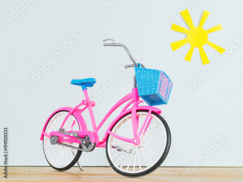 Plexiglas Fiets Pink model of children's Bicycle on the wooden floor against the background of the toy sun.