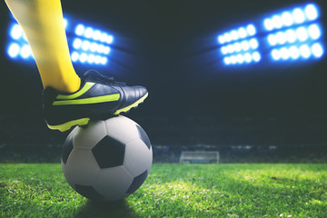 Closeup of foot holding on a soccer ball on field