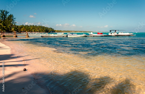 Fotobehang Blauw tropical beach with clear ocean water, coconut on the perch, a jetty with boats and yachts