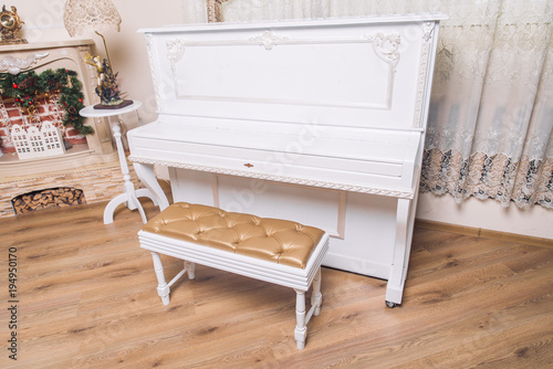Fototapeta white piano with chair in white room