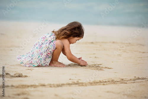 Foto op Aluminium Dubai Cute little girl playing with sand at the beach in cloudy day