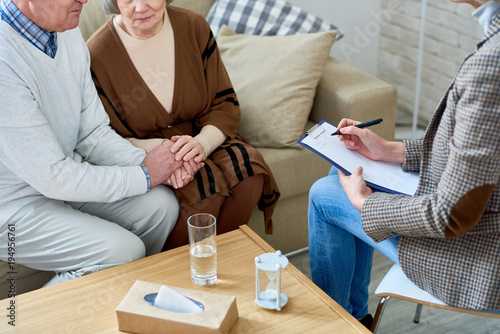Mid-section portrait of nice senior couple holding hands visiting psychologist for therapy session