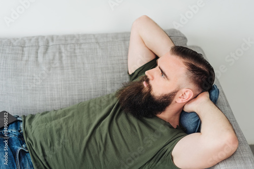 Young bearded man lying on sofa