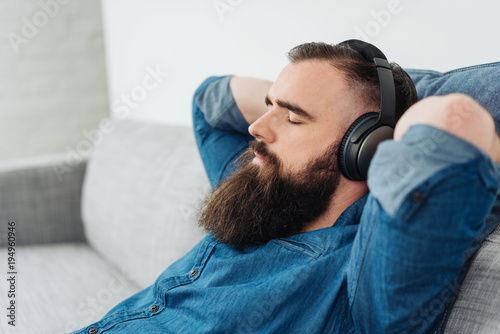 Fototapeta Bearded man listening to music on headphones