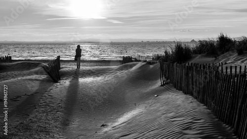 Frau am Strand bei Sonnenuntergang monochrom
