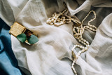 Antique beads and a ring in a gold box on a fine fabric