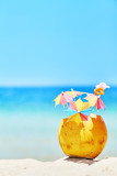 Coconut with colorful umbrellas and straws on a beach, summer fun holiday concept, selective focus, space for text.