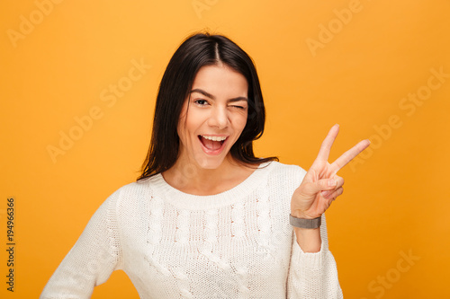 Portrait of a happy young woman showing victory sign
