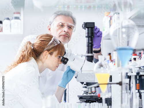 Health care researchers microscoping in life science laboratory. Young female research scientist and senior male supervisor preparing and analyzing microscope slides in research lab.