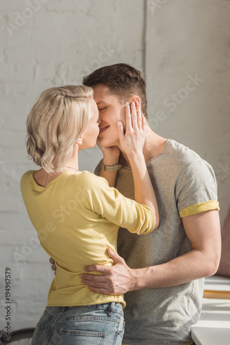 sensual couple standing and kissing at home
