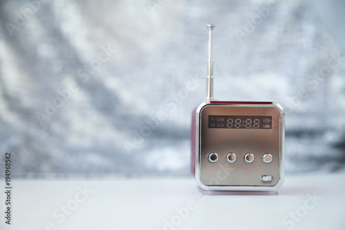 Cute little modern radio with antenna on a gray background. New reflecting cube radio receiver with copy space. Wireless hi-tech electronic mass media equipment
