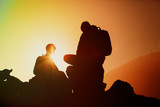 Silhouettes of father and son hiking in mountains at sunset