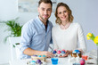 Happy young man and woman coloring Easter eggs