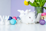 Bunny in nest on table by Easter eggs