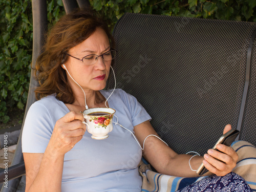 A middle aged woman with cup of coffee and  phone  resting in garden.