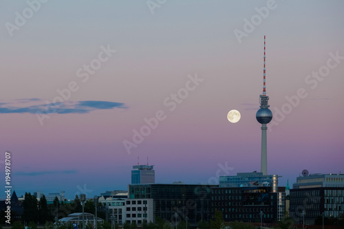 Papiers peints Berlin A full moon beside the Berlin TV tower on a peaceful evening sky with urban landscape