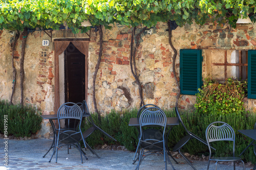 Tuinposter Toscane Tables and chairs near the entrance to the old cafe, Italy