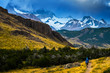 Hiker walks on the trail with mountains on the background. Patagonia, Argentina