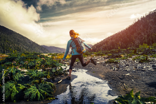 Woman hiker jumps over the small river. Hiker crossing the river in a valley with lush vegetation surrounded by mountains