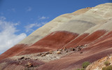 Capitol reef, central Utah, USA. View from road to big red and yellow clay hill with beautiful clouds in blue sky.