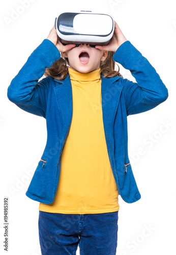 Happy little girl wearing virtual reality goggles watching movies or playing video games. Cheerful smiling teenager looking in VR glasses. Funny child experiencing 3D gadget technology - close up.