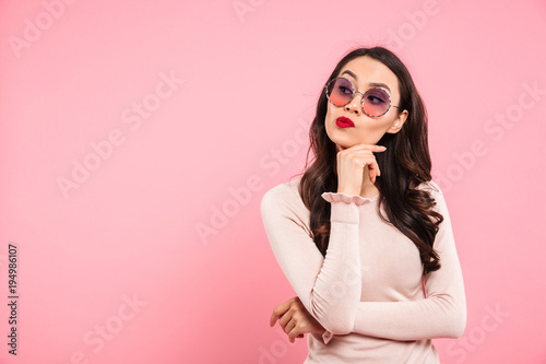Photo of dreaming adult girl with red lips wearing trendy sunglasses looking aside touching chin with hand, isolated over pink background