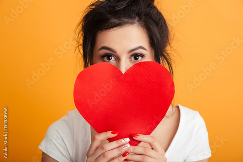 Plexiglas Hoogte schaal Closeup imege of nice girl 20s in casual t-shirt covering her face with paper red heart and expressing love, over yellow background