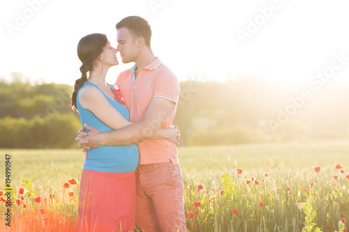 Young beautiful pregnant couple in poppy field