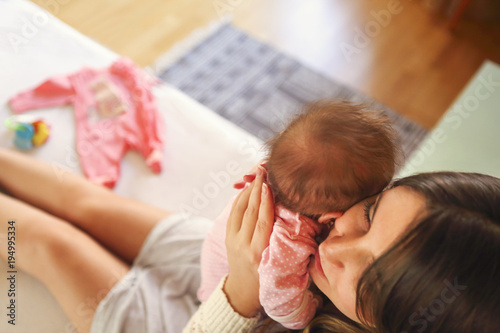 Young mother holding her newborn child. Mom nursing baby. Family at home