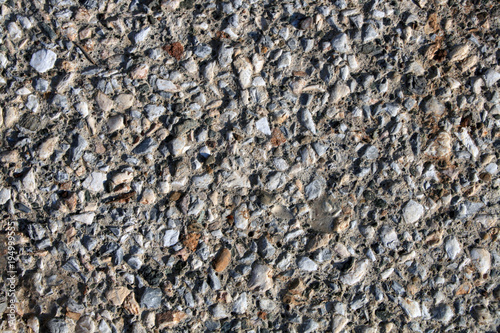 Foto op Canvas Stenen Gravel stones in the concrete. Different sized gravel stones are built into a concrete wall that is exposed to natural sunlight. Pebbles are mostly gray. In between are white, brown and black stones.