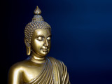 Golden antique buddha statue. The background is midnight blue. The face of the Buddha turned to the Left.