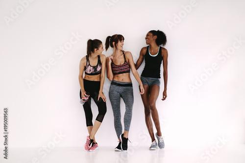 Staande foto Wanddecoratie met eigen foto Group of sporty girls talking in fitness studio