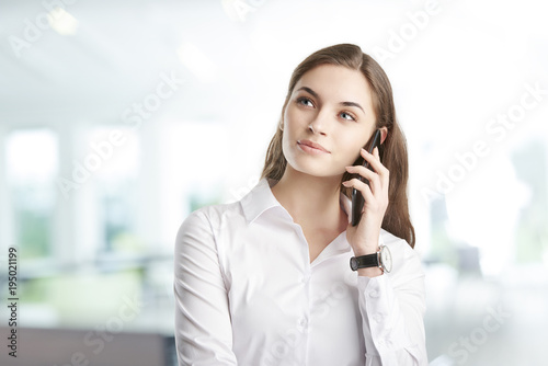 Young professional woman with her cellphone. Attractive young financial assistant businesswoman talking with somebody with her mobile phone while standing at the office.