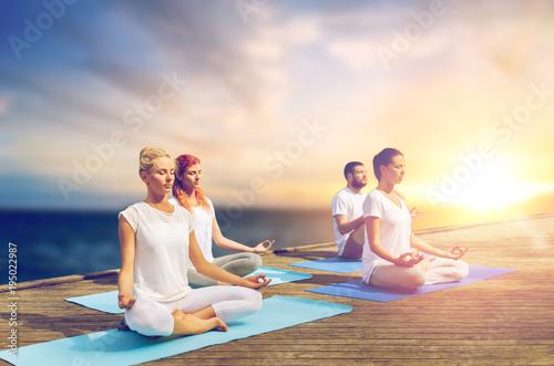 Aluminium School de yoga people meditating in yoga lotus pose outdoors