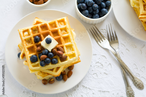 Healthy breakfast. Belgian waffles with butter, blueberry and nuts on white tablecloth. Selective focus