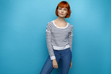 Beautiful woman with red hair isolated on blue background