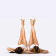 Shapely female legs. Portrait of two beautiful young women on a gray background