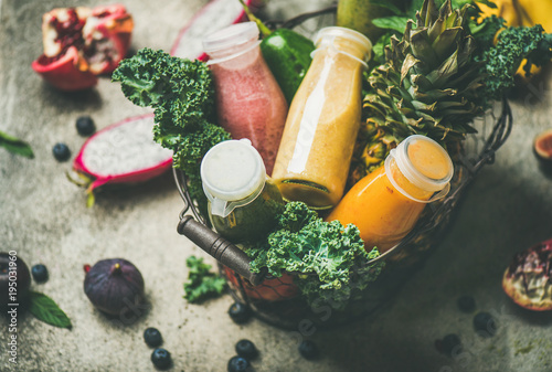 Foto op Canvas Sap Colorful smoothies in bottles with fresh tropical fruit and greens in basket on grey concrete background, selective focus. Healthy, vegetarian, detox, dieting, clean eating breakfast food concept