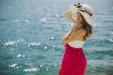 Young attractive woman with a hat poses by the sea at sunny day