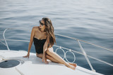 Pretty woman relaxing on the yacht on sea at sunny day - 195033376