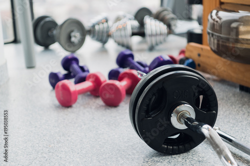 set of equipment for weightlifting and fitness: dumbbells, barbell and rowing machine at gym