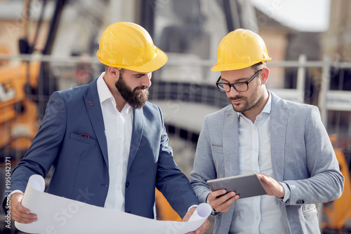 Two engineers in hardhat is using a tablet computer. © ivanko80