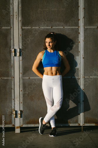 Fit young woman taking a urban workout rest. Female athlete wearing fitness sportswear.