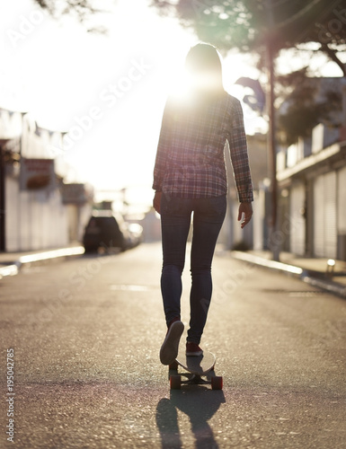 Girl riding on a longboard in sunset light